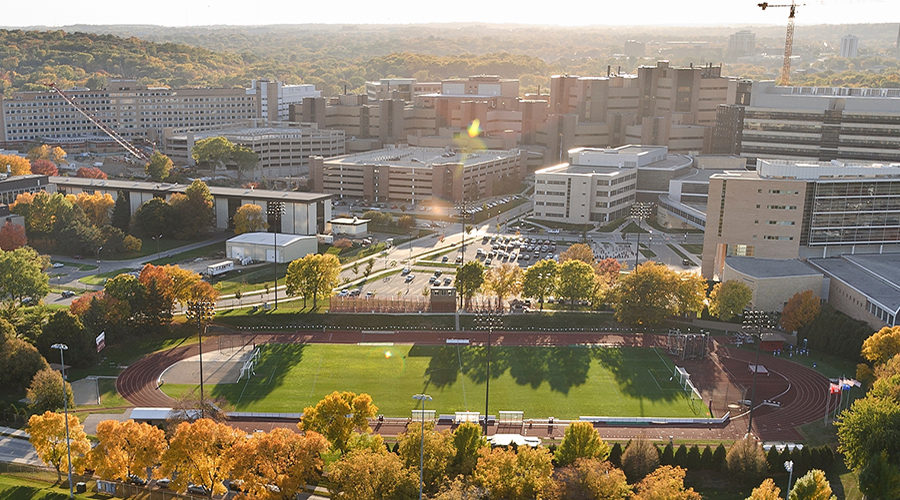 Major campus facilities pictured from counterclockwise from bottom include the UW Marching Band practice field, McClimon Complex (track and soccer field), Rennebohm Hall, Health Sciences Learning Center, Wisconsin Institutes for Medical Research, UW Hospital and Clinics, Veterans Administration Hospital, and WARF Office Building. The photograph was made from a helicopter looking southwest.