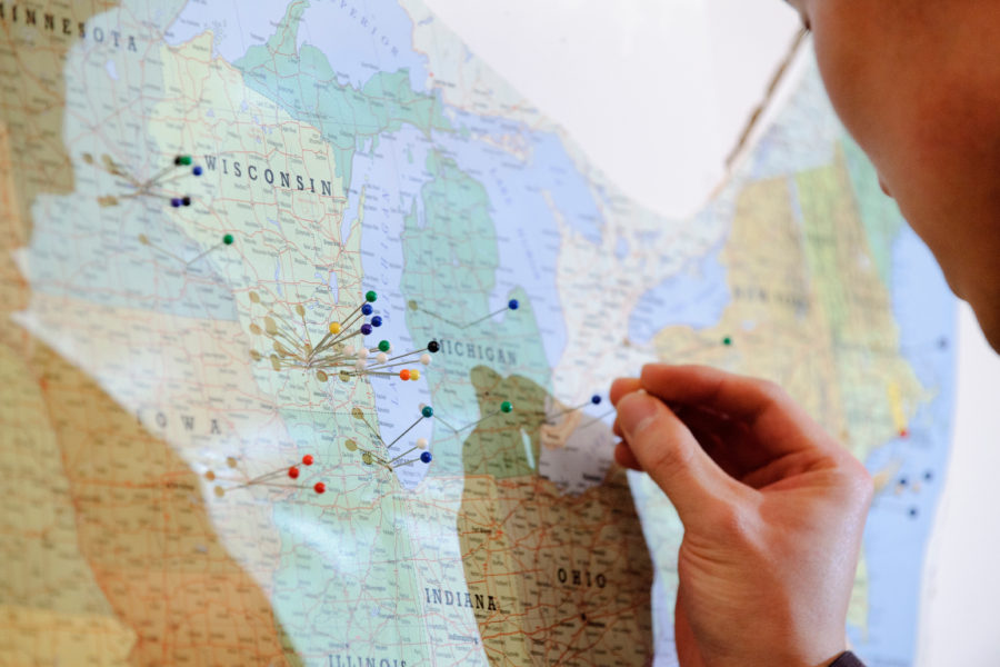 A soon-to-graduate medical student uses a push pin to mark on a United States of America map the destination of their just-announced residency