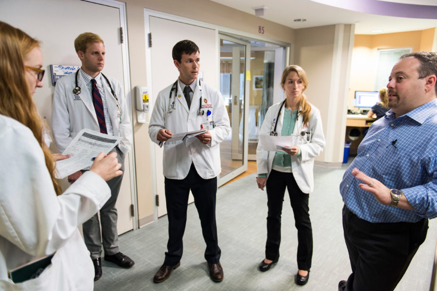 The medical director of the Neurocticial Intensive Care Unit at UW Hospital and Clinics talks to a group of medical students during floor rounds