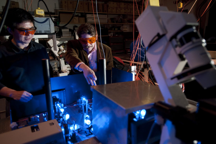 Shiguo Zhou (left) and David C. Schwartz look at the path that blue laser light follows through focusing optics and beam splitters
