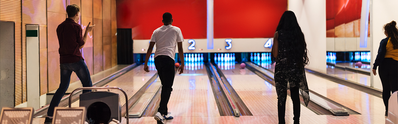 Four people at a bowling alley using lanes 1 through 4. Each is waiting for their ball to hit the pins. Picture by rawpixel on unsplash.