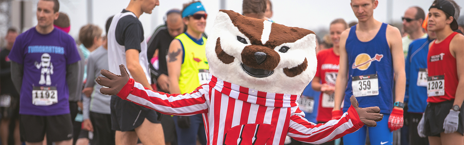Bucky Badger with arms spread wide in front of a crowd of people wearing running clothes.
