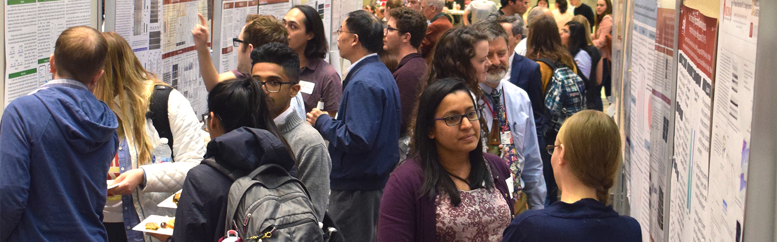 Attendees of the 2019 UWCCC Research Retreat participate in the scientific poster sessions, crowding between rows of poster boards.