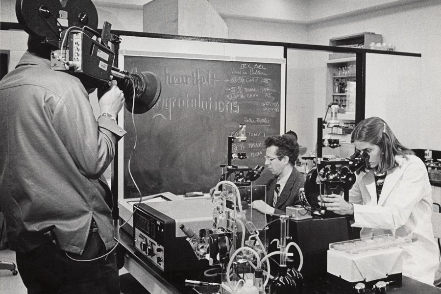 A man films Howard Temin, 1975 Nobel Prize in medicine and professor of oncology at the McArdle Laboratory, and a student at work in the lab.