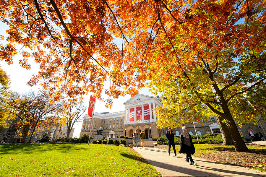 Students walk along a colorful tree-lined sidewalk outside Bascom Hall in fall at the University of Wisconsin-Madison