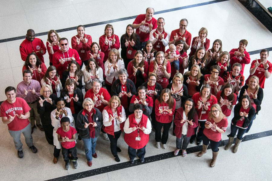 UW staff dressed in red holding up their hands in the shape of a W