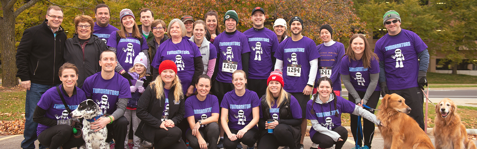 A team of UW Carbone's Race for Research participants and three of their dogs, mostly in dark purple, poses for a photo.