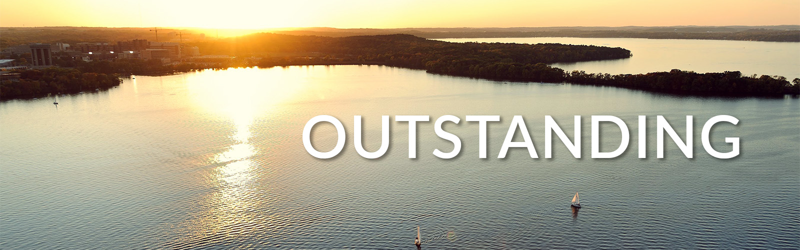 "The word ""Outstanding"" is overlayed on a photo of sailboats dot Lake Mendota in an aerial view of the University of Wisconsin-Madison campus shoreline during an autumn sunset. On the horizon at right is a silhouette of Picnic Point, to the left is the medical campus."