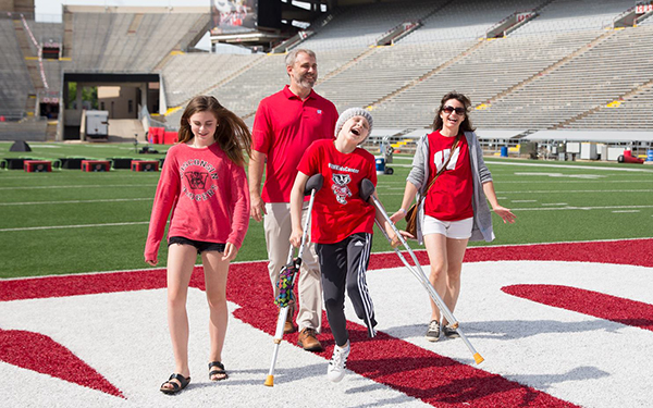 A patient skips down the field joyfull at Camp Randal with their family.