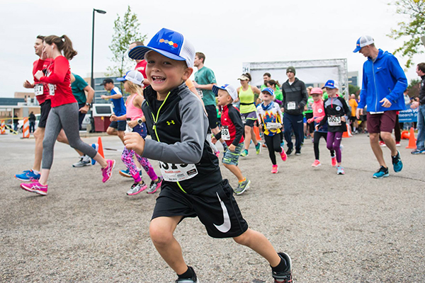 A child in a baseball cap smiles for the camera while running at Carbone's Race for Research, with other runners in the background.