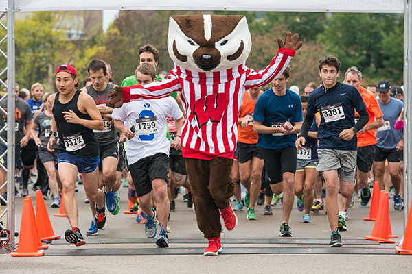 Bucky crossing the starting line at Race for Research, followed by other racers.