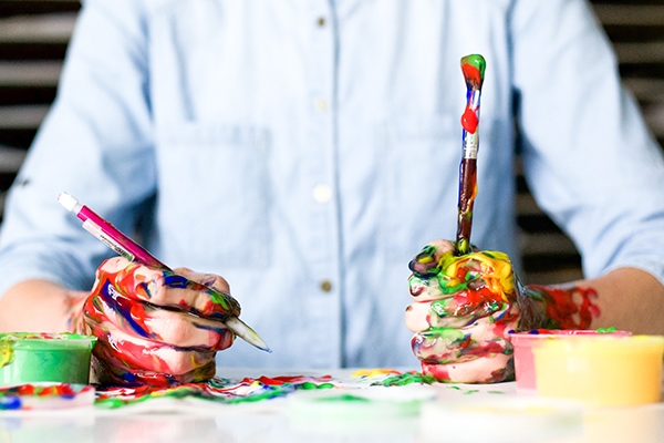 A person with paint on their hands, holding a paint brush and pencil in either hand.