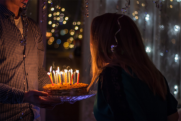 One person holding a cake with lit candles on it so that a second person can blow out the candles. By Sergei Solovev.